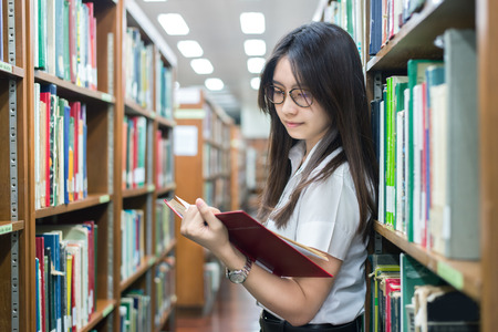 Asian student in uniform reading in the library at university