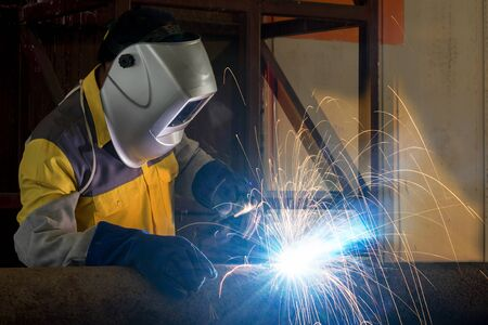 erecting: close up of worker with protective mask welding metal