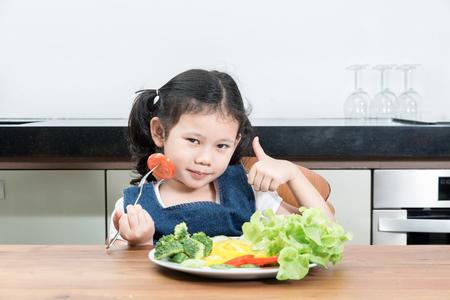 niños comiendo: Pequeña muchacha asiática con vegetales de alimentos