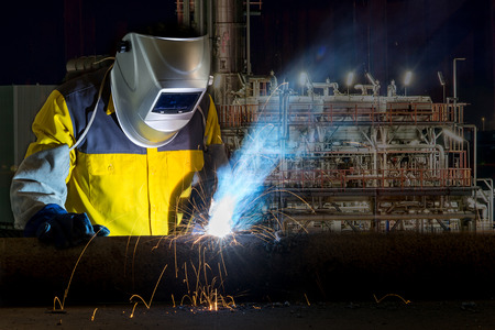 metal: Worker with protective mask welding metal