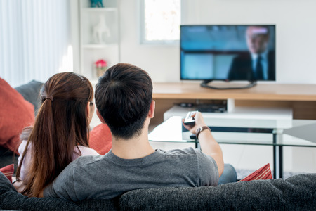 woman watching tv: Rear view of Asian couple watching television in living room