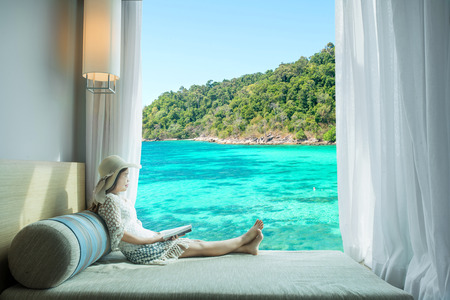 Summer, Travel, Vacation and Holiday concept - Asian woman looking sea view at window in resort, Phuket ,Thailand