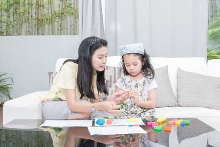 clays: family, children and happy people concept - Asian mother and kid daughter playing with plasticine in home