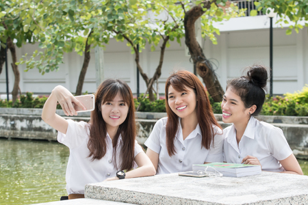 asian adult: Happy friends taking self portrait through smart phone in college