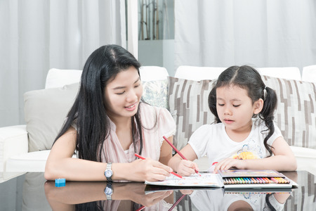 family, children and happy people concept - mother and daughter drawing at home Stock Photo