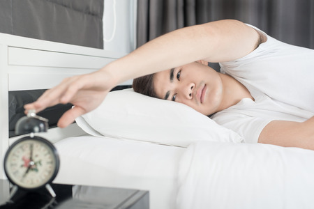 wake: Asian man lying on the bed and stopping alarm clock