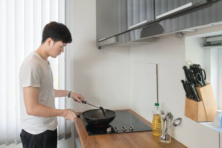 Asian Handsome man cooking in the kitchen at home