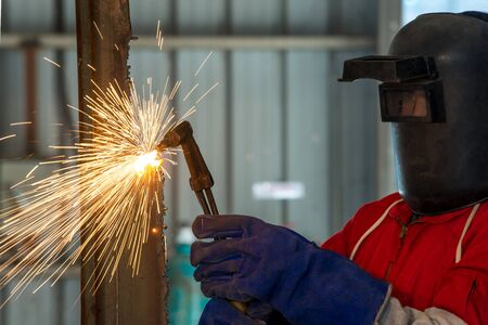 prefabricate: Worker with protective mask welding metal in factory