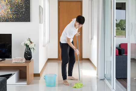 chores: Asian young man cleaning floor at home