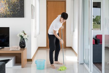 orden y limpieza: piso de la limpieza del hombre joven asiático en el hogar