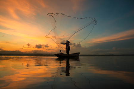 entrapment: Fisherman fishing at lake in Morning, Thailand. Stock Photo
