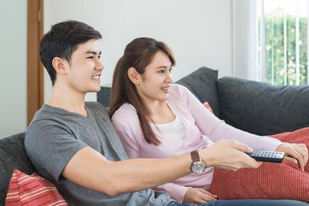 ver tv: Pareja joven de Asia waching película en la televisión en el hogar