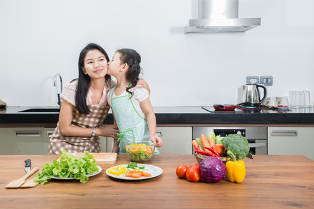 asian cook: family, children and happy people concept - Asian mother and kid daughter cooking in the kitchen at home
