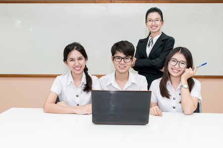 Asian teacher assisting student using laptop at desk in classroom Imagens