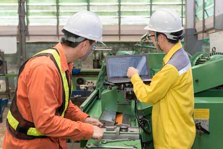 young engineer: Engineers and worker discussing work together in factory