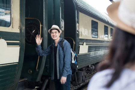 Handsome Young Asian man say goodbye to girlfriend at train station before journey