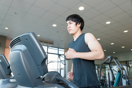 asian guy: Asian young man running on treadmill in gym