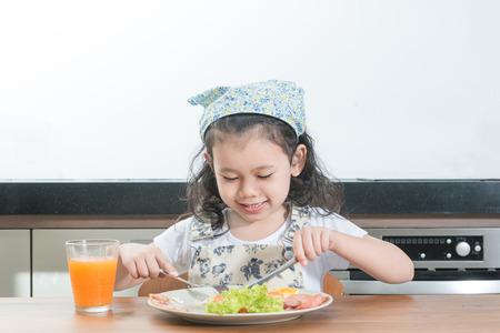 familie, kinderen en gelukkige mensen concept - Aziatisch meisje kind het eten van Amerikaans ontbijt in huis Stockfoto