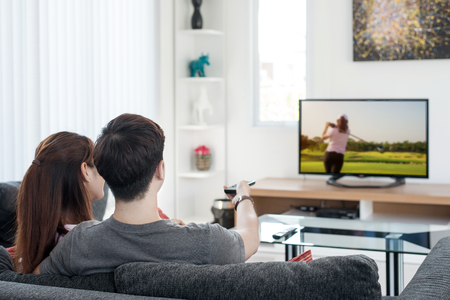 family movies: Young Asian couple waching golf sport on tv at home