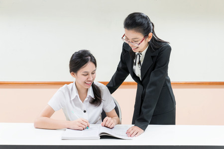Teachers guide something to asian student in uniform at classroom