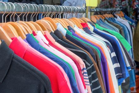 camisas: Vista frontal de las camisas de polo en la percha. camisas de polo de colores en la tienda al por menor. Cierre de las camisas de polo en la tienda al por menor