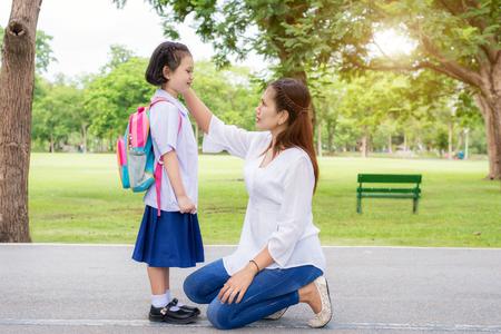 Terug naar school. Gelukkig Aziatische moeder met kinderen leerling op school. Aziatische moeder het instellen kids student shirt in school. Stockfoto