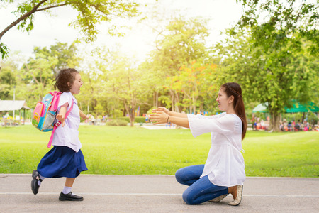 La familia, los niños y la madre - Niños estudiante funcionamiento en manos de la madre para abrazarla. Familia que se divierte en el parque. Niños es feliz de conocer a su madre