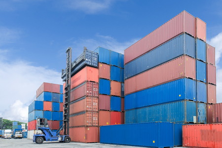 stacker: Import, Export, Logistics concept - Crane lifter handling container box loading to truck use for cargo import, export, logistics background. Stock Photo