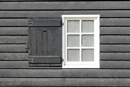 open country: Black old wood window in country house. White window on black wooden wall. Window is open.