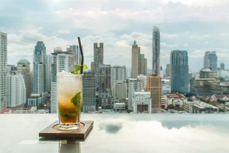 バンコク市街の景色を望む屋上バーのテーブルでカクテルのモヒートは、タイのバンコクでポイントします。バンコクの美しい屋上バー。 写真素材