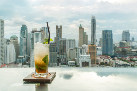 bars: Mojito cocktail on table in rooftop bar with Bangkok city view point in Bangkok Thailand. Beautiful rooftop bar in Bangkok. Stock Photo