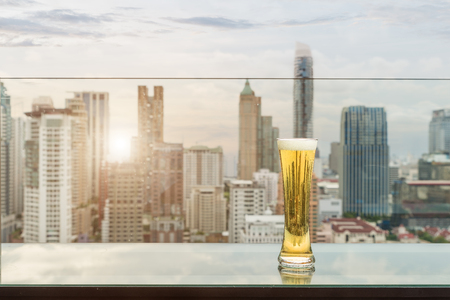Beer and foam beer on table in rooftop bar in Bangkok, Thailand.