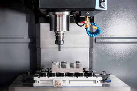 EDM or CNC industry machine working with coolant injection in industry factory. Low light.