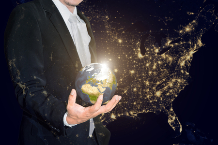 small world: Business man holding the small world in his hands against america city night light.Save our planet earth ecology concept.