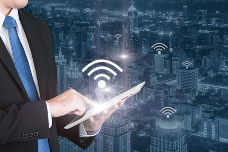 wifi: Business technology concept - Business man press digital tablet to connecting wifi or internet in business center district. Stock Photo