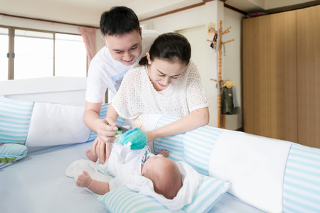 Happy family concept - Asian family with father and mother playing 2 month infant baby in bed at home.