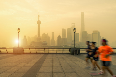 huangpu: People running in morning at Huangpu River riverside with Shanghai downtown in background in Shanghai, China. Stock Photo