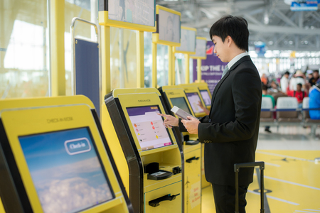Business travel - Asian business man using self check-in kiosks in airport. Technology in airport.