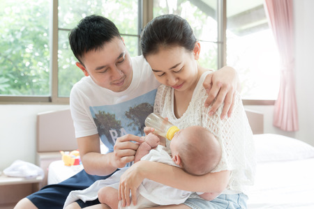 Feeding Baby infant. Asian family with mother and father feeding milk to her newborn baby infant with feeding bottle.Happy family concept. Stock Photo