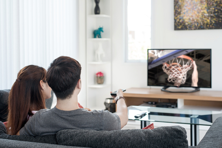 ver tv: Pareja asiática joven que ve juego del deporte de baloncesto en la televisión en casa. Disfrutar viendo baloncesto.