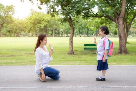 Retour à l'école. mère asiatique dire au revoir à sa fille étudiante dans le parc à l'école avant l'étude. mère asiatique envoyé signe de la main au revoir.