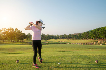 woman golf: Asian woman golf hit sweeping golf course in the summer.Golf sport concept.