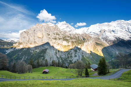 the bernese oberland: Green fields and famous stunning touristic town with high cliffs in background, Lauterbrunnen, Bernese, Oberland, Switzerland, Europe