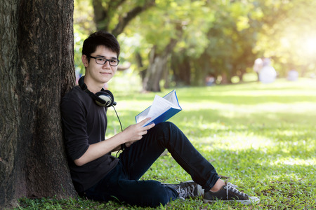 asian guy: Asian young handsome man student reading book in nature. One student.