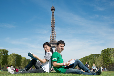 thai student: Asian couple student reading book together at outdoors park near Eiffel Tower in Paris, France. Abroad study in Paris, France.