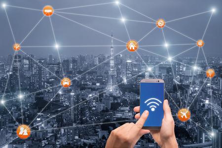 東京都市景観と wifi ネットワーク接続でスマート フォンを持っている手。スマートシティ ネットワーク接続の概念