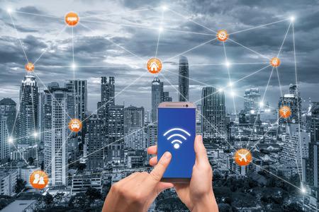 방콕의 도시 풍경과 와이파이 네트워크 연결과 손을 잡고 스마트 폰입니다. 스마트 도시 네트워크 연결 개념