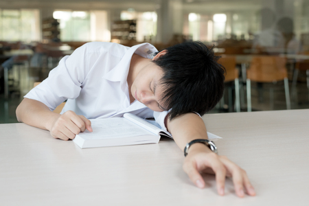 asleep: Tired Asian student or Asian young man with books sleeping in library at university. Student, education, session, exams and school concept.