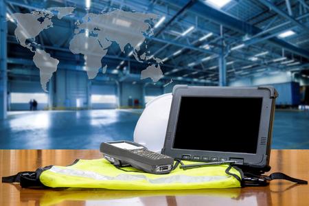 世界地図で近代的な倉庫の前に頑丈なコンピューターのタブレットとバーコード スキャナー。物流コンセプト。