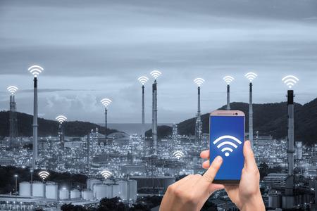 Hand hält Smartphone Steuerung drahtloses Kommunikationsnetz Smart Factory und Internet der Dinge. Smart-Fabrikkonzept. Standard-Bild